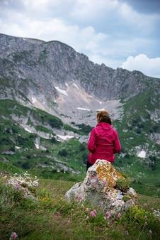 Une femme dans une veste rouge est assise sur un rocher dans une vallée de montagne et regarde au loin