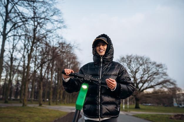 Femme dans une veste sur un scooter électrique dans un parc en automne.