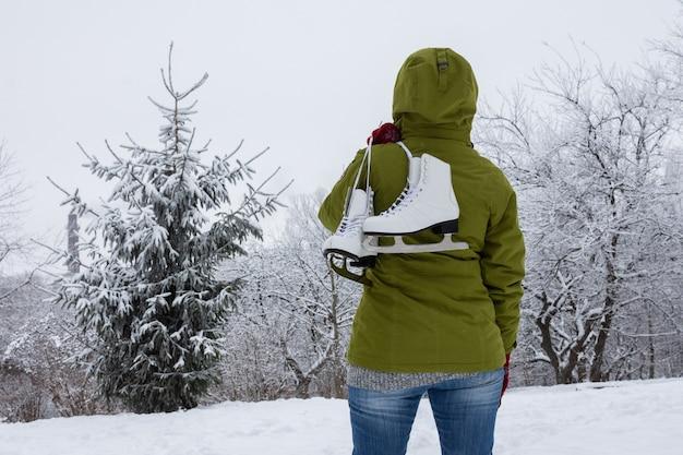 Femme dans une veste verte avec des patins à glace se penche sur la forêt enneigée
