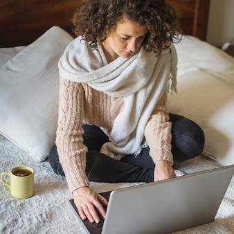 Femme dans des vêtements chauds à l'aide d'un ordinateur portable sur le lit