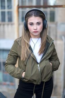 Femme dans des vêtements chauds, écouter de la musique dans les écouteurs