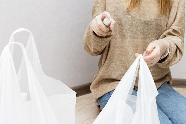 Femme dans des vêtements à la maison et des gants en caoutchouc sur ses mains désinfecte la surface des sacs en plastique avec des produits du magasin