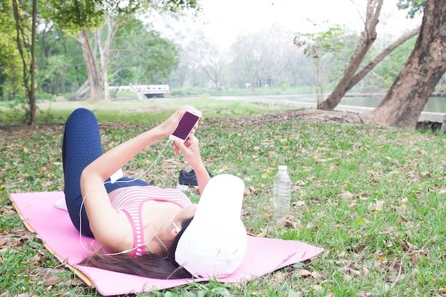 Femme dans des vêtements de sport à l'aide de téléphone portable, bien-être et concept de mode de vie sain