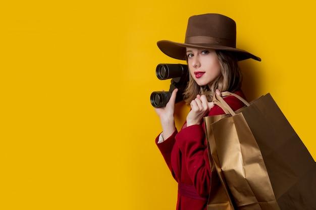 Femme dans des vêtements de style des années 1940 avec des jumelles et des sacs
