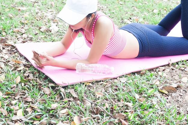 Femme dans des vêtements de yoga à l'aide de smartphone, se détendre dans le parc, mode de vie sain