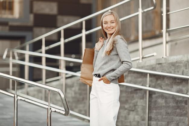 Femme dans une ville d'été. dame aux sacs marron. femme dans un pull gris.