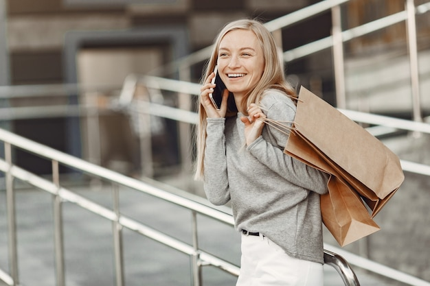 Femme dans une ville d'été. dame avec téléphone portable. femme dans un pull gris.
