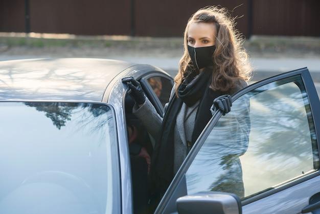 Femme dans la ville. personne dans un masque. thème du coronavirus. femme près de la voiture.