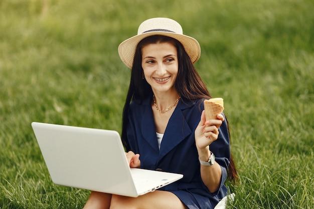 Femme dans une ville de printemps. dame avec un ordinateur portable. fille assise sur l'herbe.