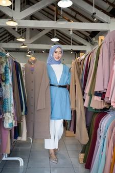 Une femme dans un voile propriétaire de magasin tenant deux robes à montrer en position debout