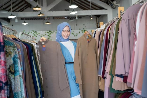 Une femme dans le voile d'une vendeuse tenant deux robes à montrer en se tenant debout