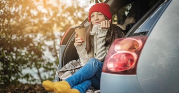 Femme dans une voiture en chaussettes jaunes en laine chaude tient une tasse de café dans les mains. week-end d'automne confortable