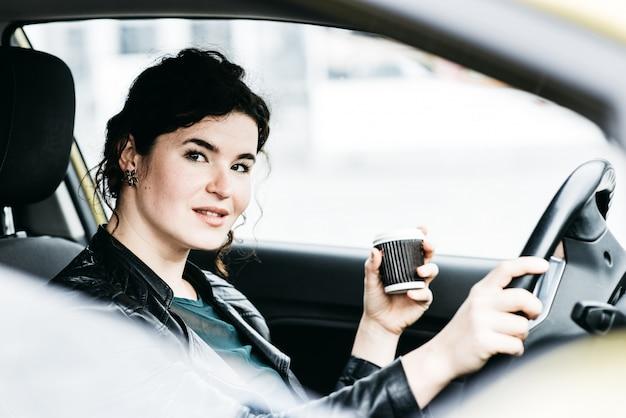 Femme dans la voiture d'intérieur garde la roue en tournant en souriant
