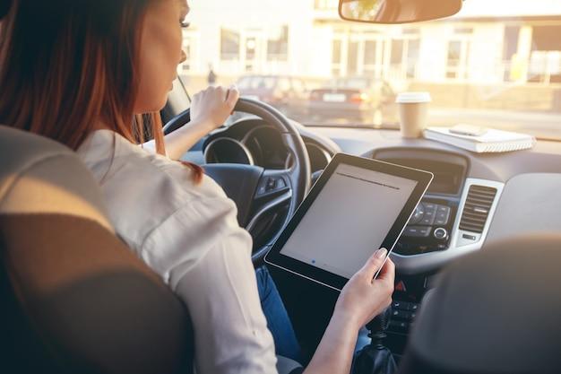 Femme dans une voiture avec une tablette dans les mains