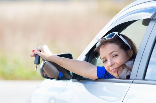 Femme dans une voiture tenant les clés en main