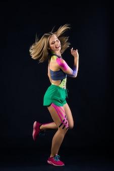 Femme dansant à l'obscurité, bandes kinésio collées sur son corps. concept de sport et de mode de vie sain