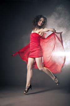 Femme dansante en robe rouge avec tissu