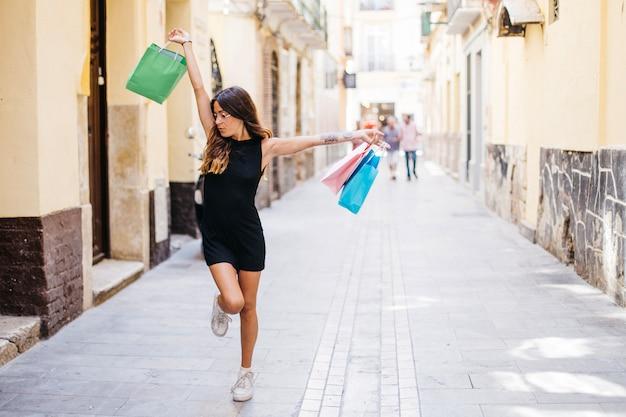 Femme dansante avec des sacs en papier