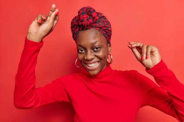 Une femme danse seule lève les bras et bouge des sourires agréablement vêtus se sent optimiste célèbre les bons résultats de travail vêtue de vêtements élégants isolés sur rouge