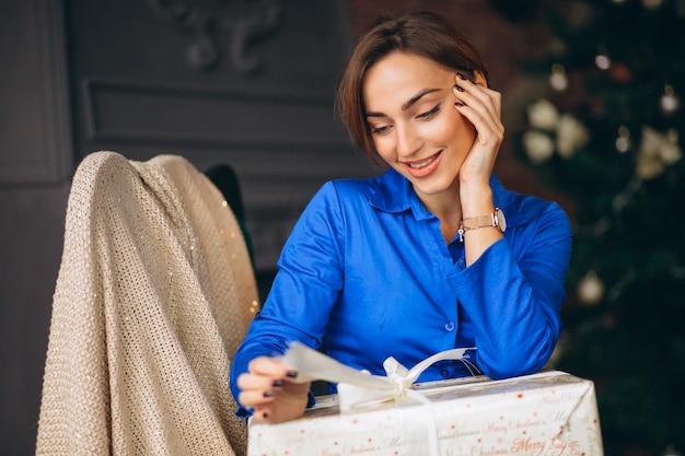 Femme déballant des cadeaux par sapin de noël