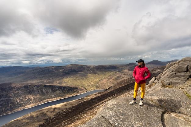 Femme debout au sommet de la montagne