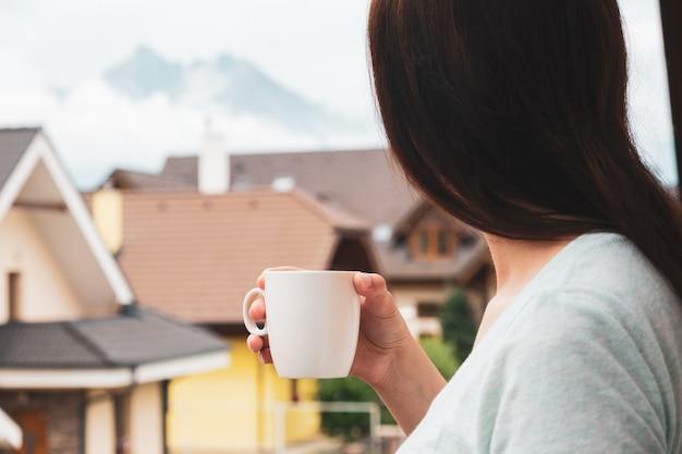 Femme debout sur le balcon et boire du thé ou du café et profiter d'une vue imprenable sur les montagnes