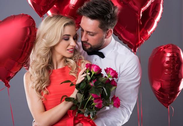 Femme debout avec un bouquet de roses coupées