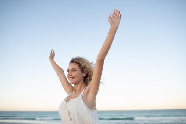 Femme debout avec les bras sur la plage