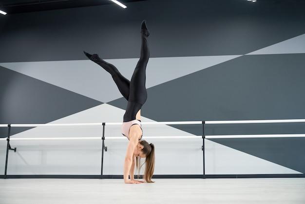 Femme debout sur les bras en studio de danse