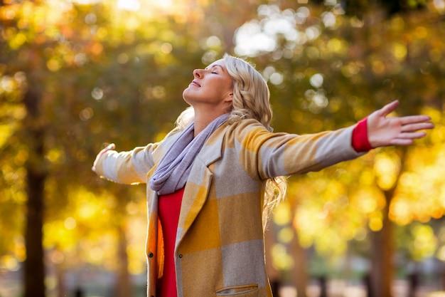 Femme, debout, bras, tendu, contre, automne, arbres