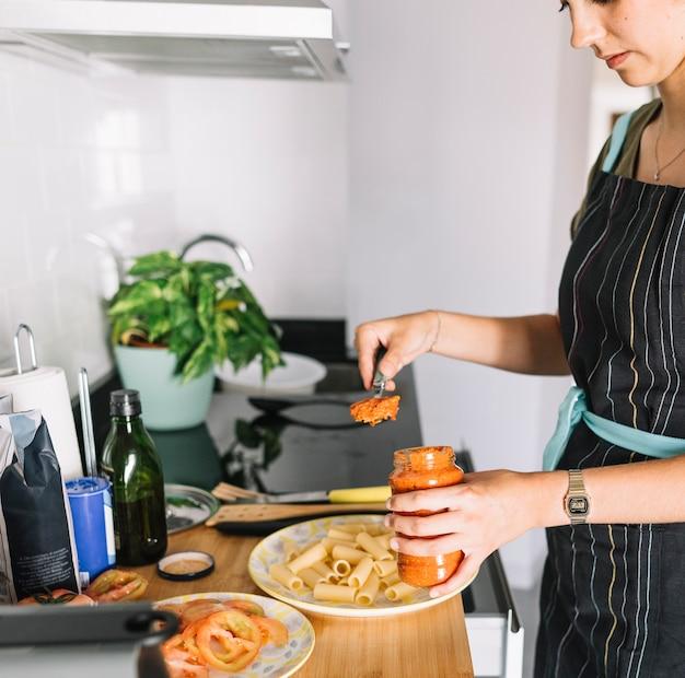 Femme, debout, à, comptoir cuisine, mettre, sauce pâtes, dans, pot