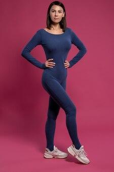 Femme debout avec confiance en combinaison de yoga sur la surface marron