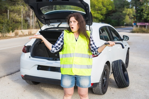 Femme debout à côté de sa voiture en panne sur la route et passer un appel en attendant l'aide d'urgence
