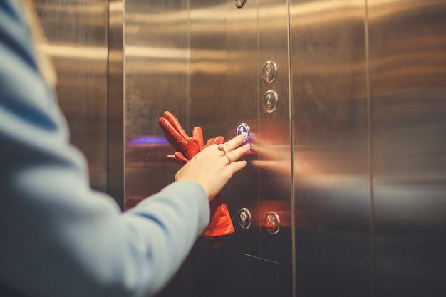 Femme debout dans l'ascenseur et en appuyant sur le bouton