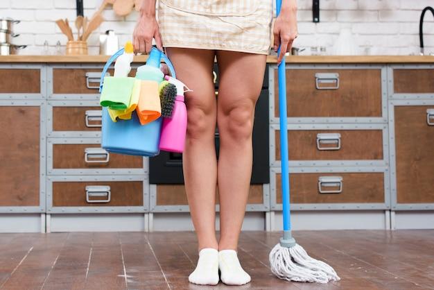 Femme debout dans la cuisine avec vadrouille et produits de nettoyage