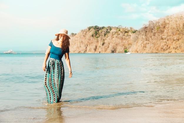 Femme debout dans l'eau au bord de la mer
