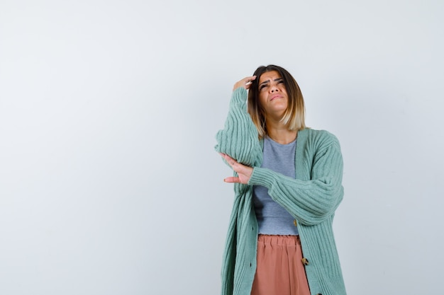 Femme debout dans la pensée pose dans des vêtements décontractés et à la sombre, vue de face.
