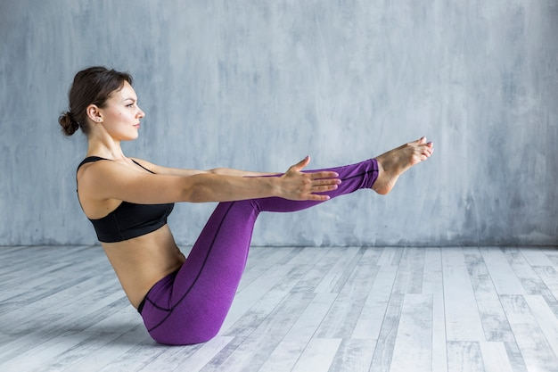 Femme debout dans une pose de yoga en bateau