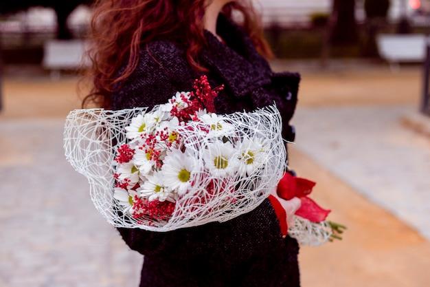 Femme debout dans la rue avec des fleurs