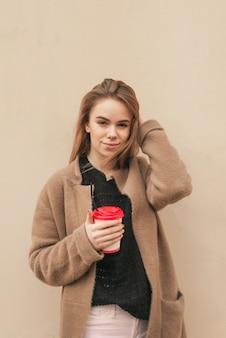 Femme debout dans la rue sur le fond d'un mur beige, tenant une tasse de café dans ses mains en regardant la caméra et en fixant ses cheveux