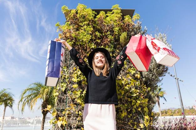 Femme debout dans la rue avec des sacs
