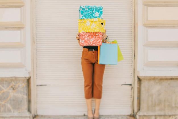 Femme debout derrière des boîtes avec des achats
