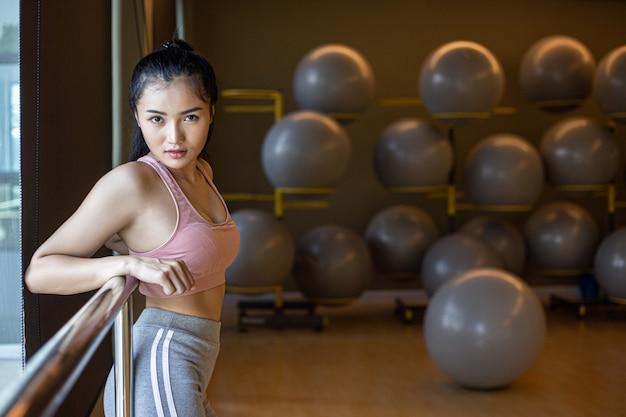 Une femme debout détendue, les mains posées sur un rail en acier dans le gymnase.
