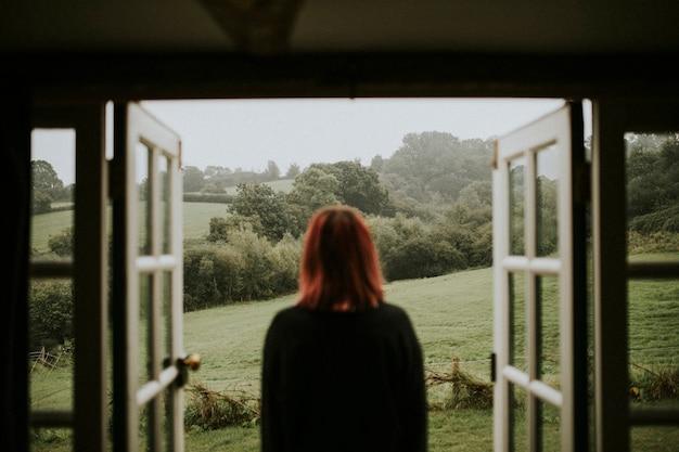 Femme debout devant la maison
