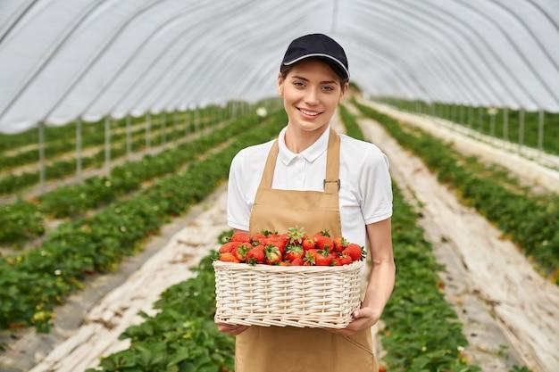Femme debout à effet de serre avec panier de fraises