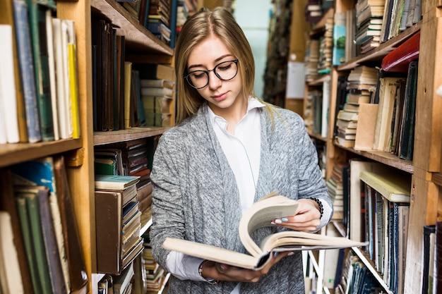 Femme debout entre les bibliothèques et tourner les pages du livre