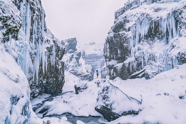 Femme debout sur une falaise couverte de neige