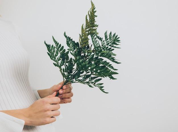 Femme debout avec des feuilles de fougère
