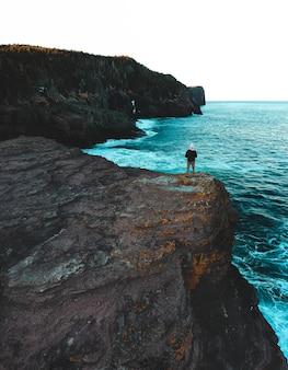 Femme debout sur une formation rocheuse près de la mer pendant la journée