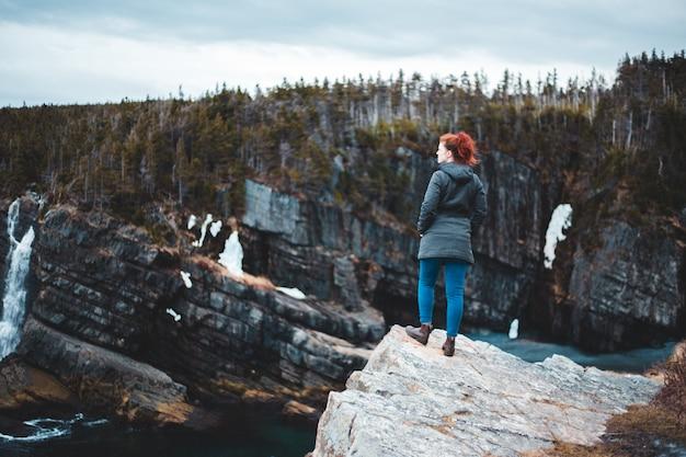 Femme debout sur une formation rocheuse près d'un plan d'eau pendant la journée
